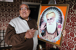 Elderly Asian man showing and holding a picture of the Guru Nanak, ***NOT TO BE USED IN THE EAST MIDLANDS***
