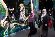 A smaller than life-size model of the Disney character Rapunzel from their company's film called Tangled stands in the window of their London store, seemingly looking out in admiration and delight at two Muslim women. Advertising the forthcoming opening of the movie, the display of the central character exemplifies feminine health, beauty, and inadvertently, of American or white European values. The ladies walk past oblivious at the attention that this fictitious person is affording them – their own lifestyle being an everyday personal choice of style and commitment to their religion. There is also the statement about femininity and gender on this urban street. Wearing long dresses that covers their bodies and the Hejab (hijab) that covers their heads, the women are a minority in this western culture.