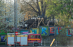 © Licensed to London News Pictures; 11/04/2020; Bristol, UK. Smoke can be seen rising from charred timbers as Avon Fire and Rescue Service and police attend a fire at the St Pauls Adventure Playground on the Saturday evening of the Easter weekend during the coronavirus lockdown. The fire damaged the wooden climbing frame and blackened the tree in the playground which is closed due to the coronavirus pandemic. The cause is not yet known. Photo credit: Simon Chapman/LNP.