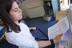 Young woman with walking frame doing some photocopying in an office,