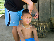 A young Hmong boy having a haircut in Ban Tatong, Phongsaly province, Lao PDR. The remote and roadless village of Ban Tatong is situated along the Nam Kang river (an offshoot of the Nam Ou) and will be relocated due to the construction of the Nam Ou Cascade Hydropower Project Dam 7.