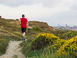 Rear view of man trail running on the cliff of Getxo