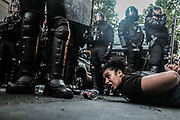 Paris, France, 03/06/20 | A young woman holds her hands behind her back while lying on the ground in front of French riot police during clashes between Black Lives Matter protesters and police who are trying to keep them from entering Paris's city center.