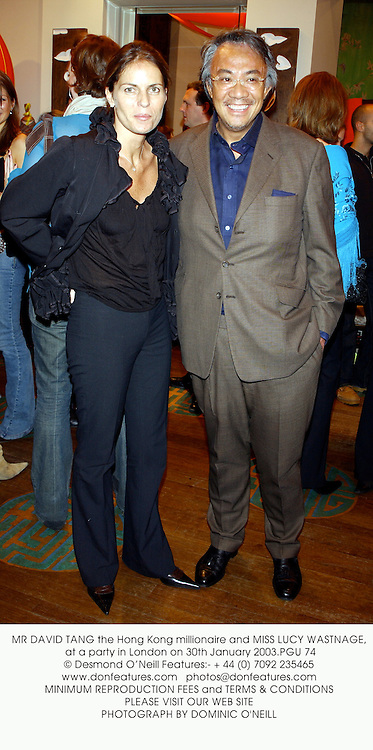 MR DAVID TANG the Hong Kong millionaire and MISS LUCY WASTNAGE, at a party in London on 30th January 2003.PGU 74