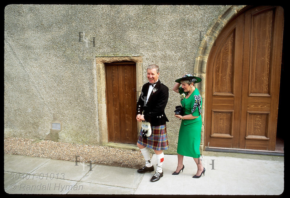 Man in kilt and wife in Easter-green dress exit church after wedding on April day; Anstruther Scotland