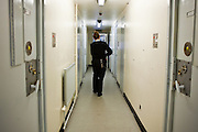 A female prison officer walks donw the corridor of one of the residential wings. HMP Send, closed female prison. Ripley, Surrey.
