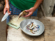Imelda Esgana, fish vendor preparing lunch at home for her children, Talisay, Bantayan Island, The Philippines. Every morning at 7 am Imelda meets the fishermen as they return from the sea with their catch. After sorting and weighing,  Imelda sells the fish locally by going house to house. Imelda and her family eat what is left over after her sales. On November 6 2013 Typhoon Haiyan hit the Philippines and was one of the most powerful storms to ever make landfall.  Three-quarters of the island's population of about 136,000 depend on fishing as their main source of income. Thousands lost their boats and equipment in the storm. Oxfam is working to support the immediate and long-term needs of affected communities on Bantayan Island.