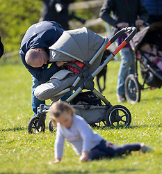 Mike Tindall with his daughters Mia (front) and Lena Elizabeth (in buggy) at the Land Rover Gatcombe Horse Trials, on Gatcombe Park, Gloucestershire.