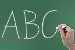 Close up of person's hand writing 'ABC' on chalkboard, Bavaria, Germany