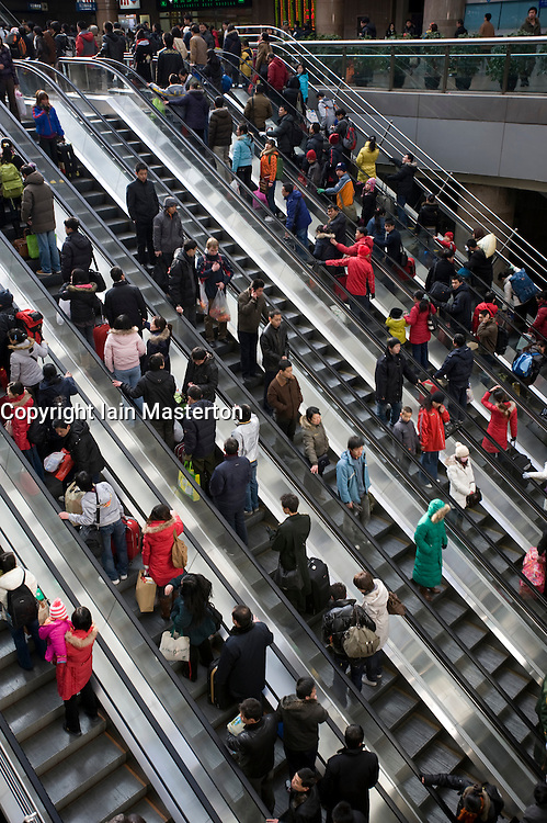 Escalators carrying passengers to trains inside Beijing West Railway Station China 2009