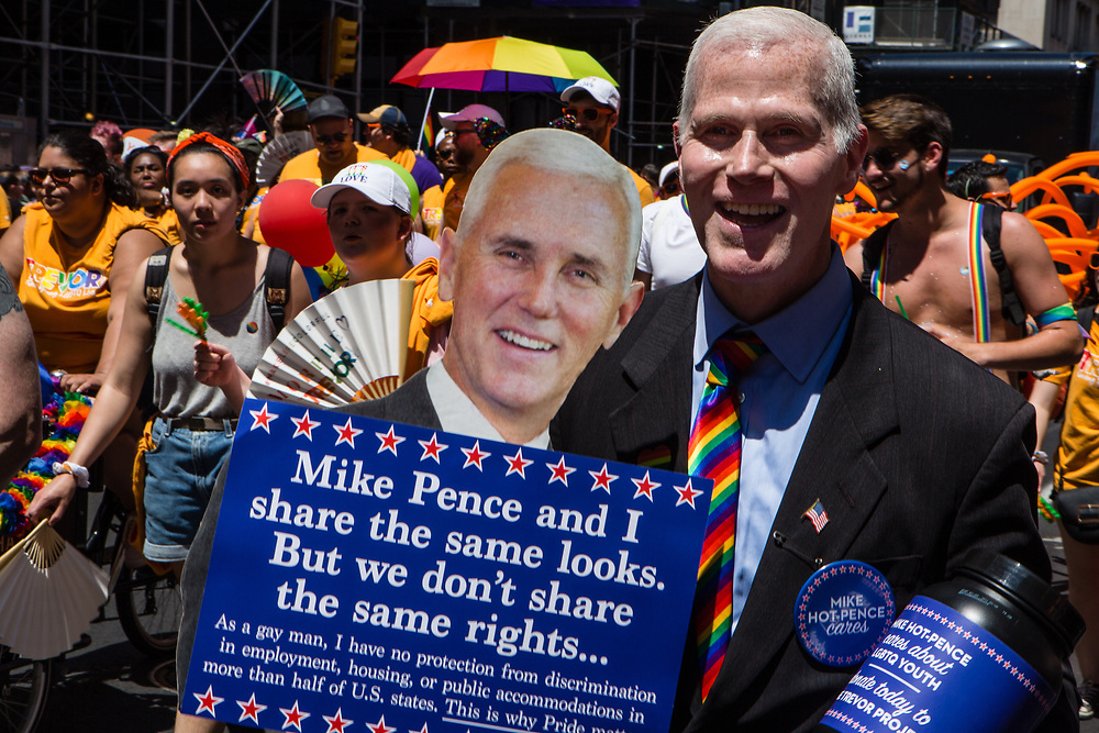 New York, NY - 30 June 2019. The New York City Heritage of Pride March filled Fifth Avenue for hours with participants from the LGBTQ community and it's supporters. A man protests the lack of rights for the LGBTQ community with a sign and portrait of American Vice President Mike Pence.