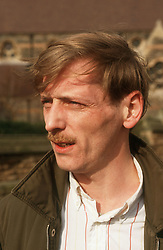 Portrait of man with moustache wearing jacket and open necked shirt,