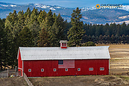 Red cattle barn with American flag near Bigfork, Montana, USA