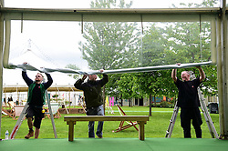 © London News Pictures. 26/05/2016. Hay on Wye, UK. The Grand Unveiling: A team of workers roll back the protective rain covers from outside the festival bookshop on the opening day of the Hay Literature Festival 2016. Photo credit: Keith Morris/LNP