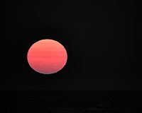 Sunset over the Pacific Ocean. There are two sunspots visible. Image taken with a Nikon N1V3 camera and 70-300 mm VR lens (ISO 160, 300 mm, f/5.6, 1/200 sec).