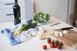 Tomatoes, mushrooms, salad, spring onions and a bottle of red wine on kitchen table
