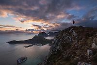 Female hiker watches midnight sun from summit of Offersøykammen mountain peak, Vestvågøy, Lofoten Islands, Norway