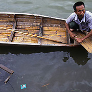 China, Cities, Ferry on Shexian River. Garbage and dead rat floating in river.