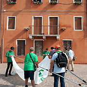 VENICE, ITALY - SEPTEMBER 18: Members of Lega Nord get ready to cover the famous window with Italian flag of Lucia Massarotto which has become the symbol of protest against Lega Nord separatist and racist ideology on September 18, 2011 in Venice, Italy. The Northern League rally is held to call for the independence of Northern Italy, during which the leader of Lega Nord pours water from the River Po in the north of Italy into the Venetian Lagoon as a symbolic rite known as Rito dell'ampolla.