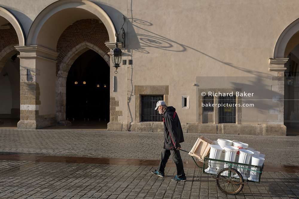 A flower seller pulls his cart after refilling buckets with fresh water from a nearby tap and past the architecture of the Cloth Hall on Rynek Glowny market square, on 23rd September 2019, in Krakow, Malopolska, Poland.