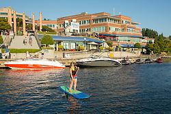 United States, Washington, Kirkland. A woman paddles a paddleboard on Lake Washington off of Carillon Point. MR