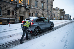 Edinburgh, Scotland, UK. 10 Feb 2021. Big freeze continues in the UK with heavy overnight and morning snow bringing traffic to a standstill on many roads in the city centre. Pic; Man pushes car up The Mound in the Old Town.  Iain Masterton/Alamy Live news