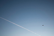 Low angle view of jet plane and vapor trail in clear sky