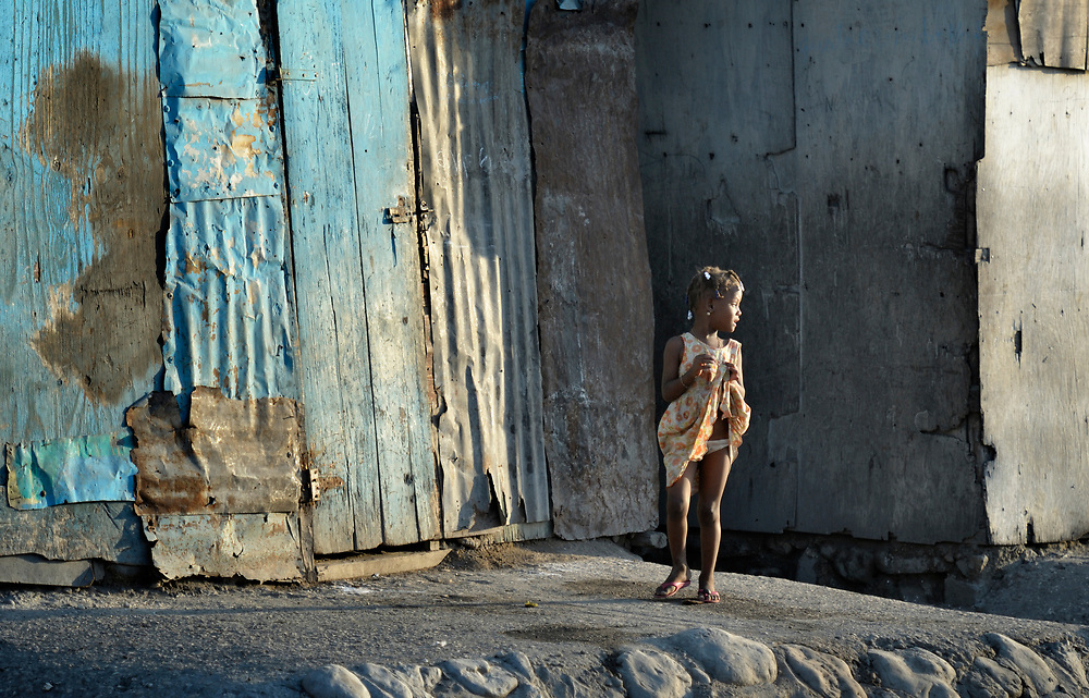 A girl stands in front of her meager home in Cite Soleil, a sprawling poor portion of Port-au-Prince, Haiti.