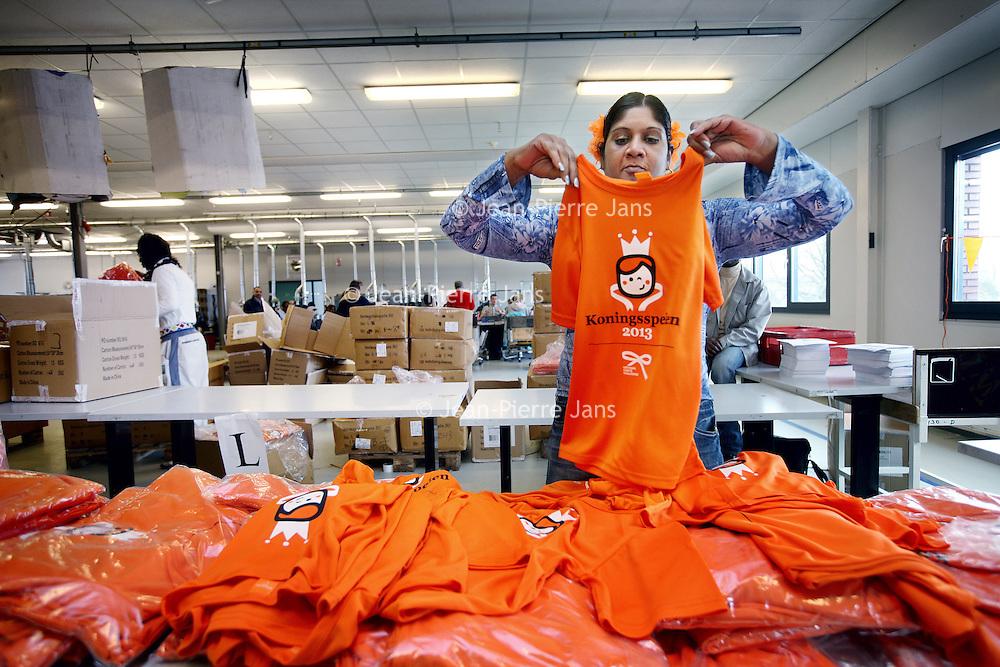 Nederland, Diemen , 17 april 2013..Sharmila van der stroom, werkzaam bij sociaal werkplaats Panter in diemen sorteert oranje shirts voor de koningsspelen..Ter ere van de troonswisseling worden op 26 april de Koningsspelen gehouden. Duizenden scholen in het land doen mee aan deze landelijke buitensport- en speldag. Alle kinderen die meedoen gaan die dag gekleed in een speciaal oranje T-shirt. Pantar Amsterdam kreeg de opdracht om deze shirts te verzorgen..Foto:Jean-Pierre Jans