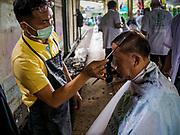 12 SEPTEMBER 2018 - BANGKOK, THAILAND: A barber checks his work on a traveler at Hua Lamphong train station in Bangkok. Barber schools set up in the station and offer free haircuts to travelers.    PHOTO BY JACK KURTZ