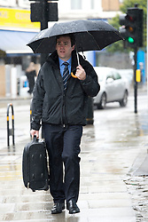 © Licensed to London News Pictures. 14/05/2012. London, UK. Shadow Health Secretary Andy Burnham MP arriving underneath an umbrella for a visit to Half Penny Steps Health Centre in North West London on May 14, 2012 where he met community nurses. Photo credit : Ben Cawthra/LNP