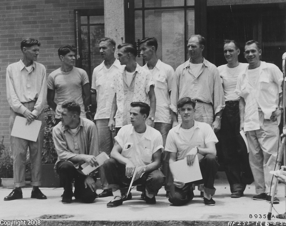 """HQ. FEAF, Tokyo --- Shown after their return to freedom in Hongkong are eleven U.S. Air Force officers and airmen, crew members of a B-29 """"Superfort"""" show down in January 1953 during a leaflet dropping mission over North Korea. From left to right, front row: T/Sgt. Howard M. Brown, St. Paul, Minn. Standing, left to right; Col. John K. Arnold, Jr., Montgomery, Alabama; A/1C Steve E. Kiba, Akron, Ohio; Capt. John M. Buck, Arthwaite, Tenn.; A/C2 John W. Thompson III, Orange, VA.,; 1st Lt. Wallace L. Brown, Montgomery, Ala.; Capt. Eugene J. Vaadi, Clayton, N.Y.; Major William H. Baumer, Lewisburg, Pa.; and Capt. Elmer F. Llewellyn, Missoula, Mont. In the picture they are still in their """"prison"""" clothing. Later they entered the Jockey Club in Hongkong got a bath, shave new clean clothing and steak dinner. August 1955."""