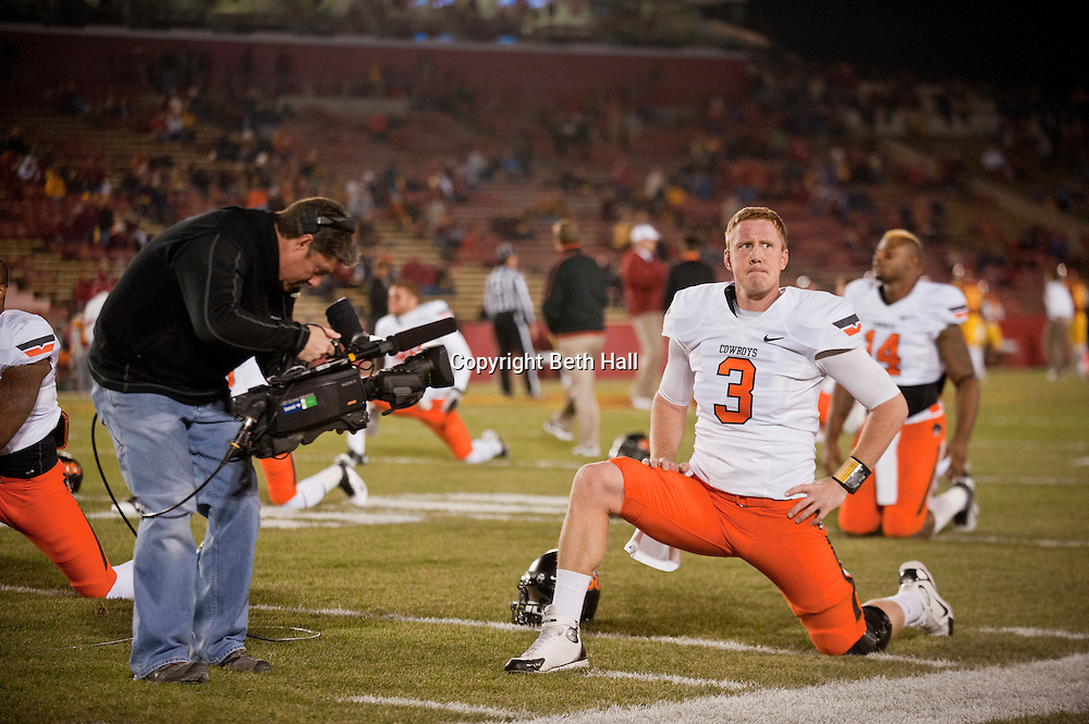 Nov 18, 2011; Ames, IA, USA; Oklahoma State Cowboys quarterback Brandon Weeden (3) is filmed as he stretches before the a game against the Iowa State Cyclones at Jack Trice Stadium. Iowa State Cyclones defeated the Oklahoma State Cowboys 37-31. Mandatory Credit: Beth Hall-US PRESSWIRE Editorial sports photography of the Iowa State Cyclones vs. Oklahoma State Cowboys in 2011 in Aimes, Iowa.