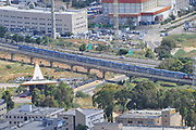 Passenger train passes through the industrial zone of Haifa Bay, Israel