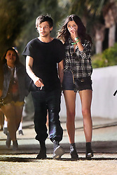 "EXCLUSIVE: Louis Tomlinson keeps his girlfriend Eleanor Calder close as they party the night away at Coachella. The two, followed along by a couple friends, and a single bodygaurd, were seen walking around the festival without ever letting go of each other's hand other than to smoke what looks like a rolled cigarette. Louis and his girlfriend were also seen enjoying ""dirty dogs"" outside of the festival grounds. 16 Apr 2017 Pictured: Louis Tomlinson and Eleanor Calder. Photo credit: Snorlax / MEGA TheMegaAgency.com +1 888 505 6342"