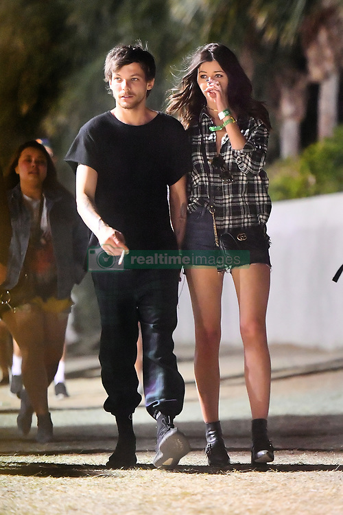 """EXCLUSIVE: Louis Tomlinson keeps his girlfriend Eleanor Calder close as they party the night away at Coachella. The two, followed along by a couple friends, and a single bodygaurd, were seen walking around the festival without ever letting go of each other's hand other than to smoke what looks like a rolled cigarette. Louis and his girlfriend were also seen enjoying """"dirty dogs"""" outside of the festival grounds. 16 Apr 2017 Pictured: Louis Tomlinson and Eleanor Calder. Photo credit: Snorlax / MEGA TheMegaAgency.com +1 888 505 6342"""