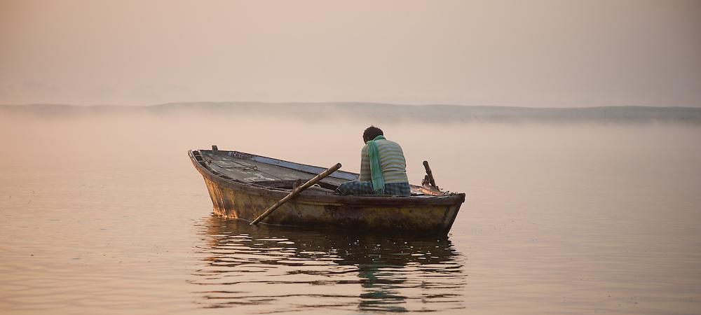Man meditating on boat on the Ganges river at Varanasi at dawn (India)