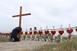 November 9, 2017 - Sutherland Springs, Texas, U.S. - JOSHUA JOHN, of Roanoke, Virginia, kneels by a memorial for the Sutherland Springs, Texas First Baptist Church mass shooting, Thursday. (Credit Image: © San Antonio Express-News via ZUMA Wire)