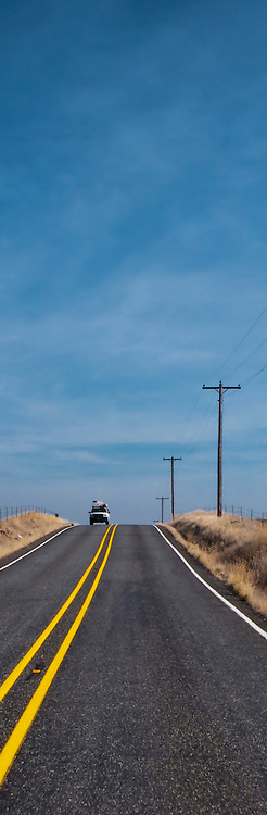 A loaded vehicle comes into view over a crest in the road in rural Klickitat County, WA, USA vertical panorama