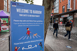 © Licensed to London News Pictures. 12/10/2020. LONDON, UK. People pass a prominent social distancing sign in Harrow town centre.  It is reported that five London boroughs had more than 100 new COVID-19 cases per 100,000 population in the week to October 8 — Richmond, Hackney, Ealing, Redbridge and Harrow.  As the UK experiences a rise in the number COVID-19 cases nationwide, Boris Johnson, Prime Minister is announcing in the House of Commons a new three-tier local lockdown system to tackle the spread of the virus.  Photo credit: Stephen Chung/LNP