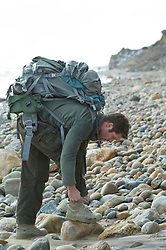 Man with a large backpack  at the beach tying his shoe