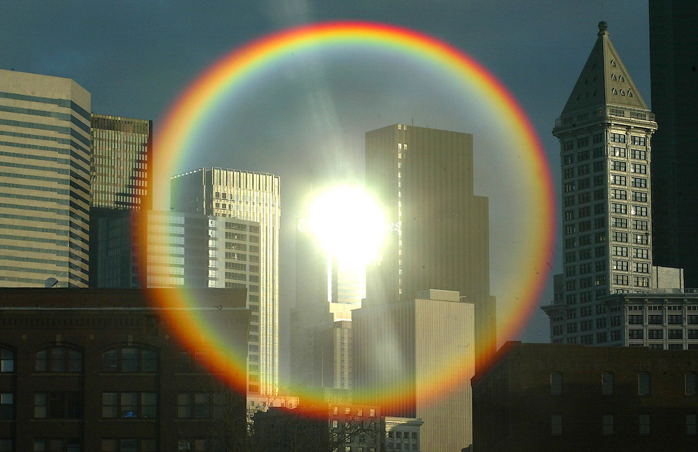 A rainbow of flare (a photographic term for the change an image undergoes when the lens is pointed directly into the sun) occurs during sunrise when the sun is reflected off a building in downtown Seattle.  The Smith tower is at right. (Steve Ringman / The Seattle Times)