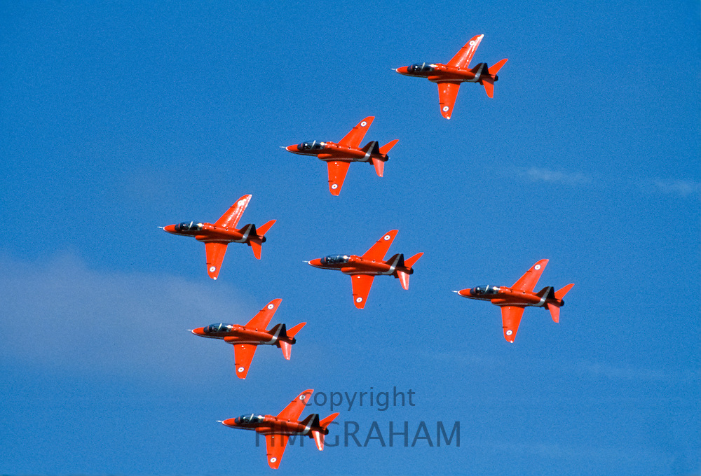 Aircraft of The Red Arrows aerobatic in flight in flying formation over RAF Scampton in Lincolnshire, England, UK