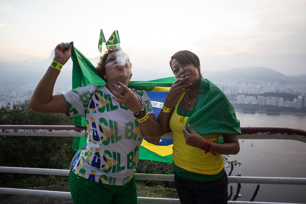 Maria Cristina Ribiero (L) and Sueli Ribiero (R) at the top of Morro da Urca, the monolith that is halfway to Sugarloaf on the cable car route. The mountain was closed for a massive private party to show the Brazil v Mexico game. Scenes from Rio de Janeiro on the day that Brazil drew 0-0 with Mexico. Photo by Andrew Tobin/Tobinators Ltd