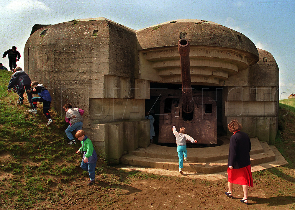 French school children rush the derelict remains of the big guns along the coast of Normandy, France on the 50th anniversary of D-Day, June 6, 1994.