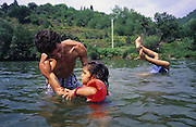 The Baptiste family swimming in the river. French Gitans, in the south of France, are full of spirit. They live as strong communal families with everyone looking after the children, living and breathing the rythmns of rhumba and flamenco music. Any chance to celebrate brings song and dance together with 'palmas' hand clapping. Some work the markets, others doing building, cleaning or maintenance work. Some live in municipal apartments others in caravans. They most often live within their own communities, distrustful of outsiders, and  experience problems of innercity life, and of racism. Roma people have suffered a history of racial persecution for centuries. Though mainly sedentary living in houses and apartments, they are still viewed from the outside as 'Les gens de voyage'. Many will holiday, take seasonal work or go to religious festival in their caravans, coming back to their house over for the rest of the year. Southern France