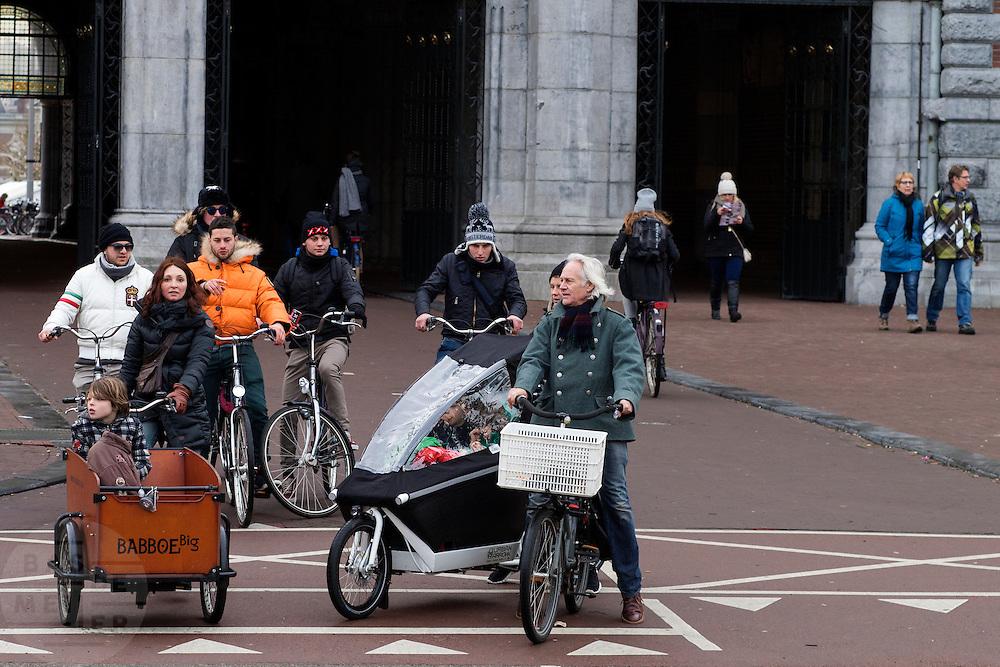 In Amsterdam wachten fietsers bij de onderdoorgang van het Rijksmuseum op een verkeerslicht. Een jongetje in de bakfiets heeft zijn hoofd verstopt in de jas.<br /> <br /> In Amsterdam cyclists are waiting at a traffic light near the passing underneath the Rijksmuseum. A boy in a cargo bike hides his head in a coat.