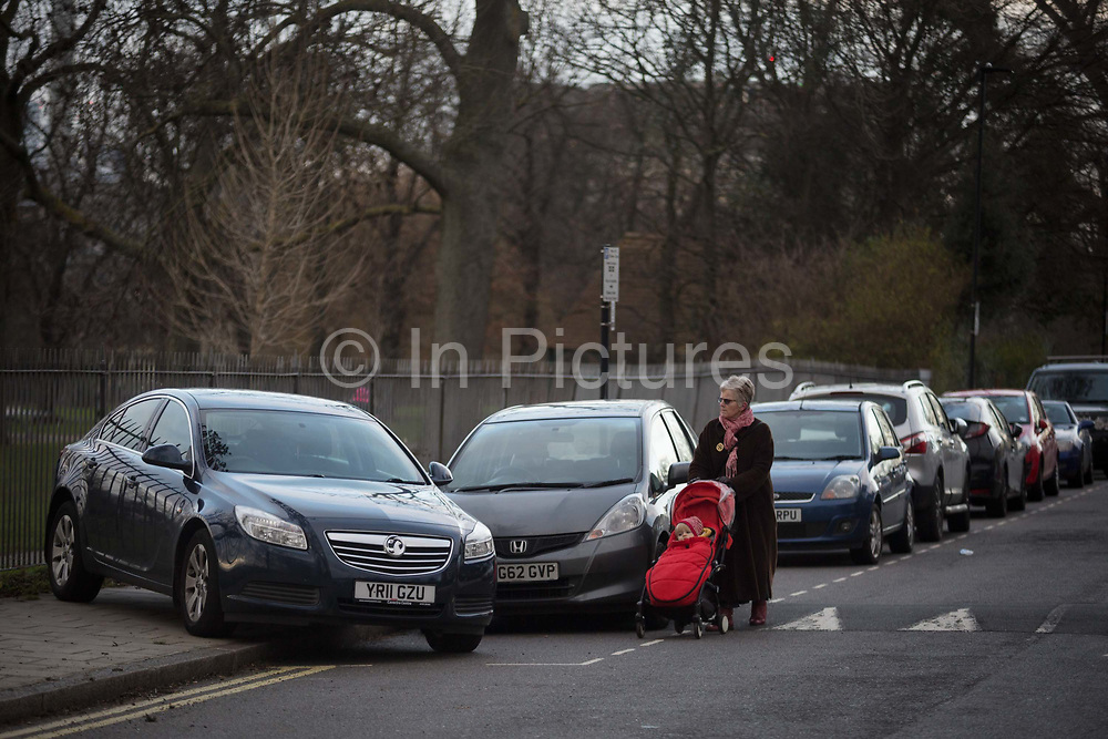 An elderly lady with a childs buggy walks in the road past a mysteriously abandoned Vauxhall car resting at 45 degrees, off the road but blocking a pavement on Ruskin Park, on 2nd February 2018, in Southwark, London, England. Because the car isnt blocking the highway, this is not a police matter - but causing an obstacle on the pavement makes it a council problem.