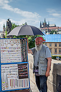 Portrait of Jan (Honsa) who is selling jewelry at Charles Bridge and protecting himself with an umbrella against the sun.
