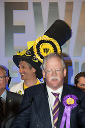 © Licensed to London News Pictures . 06/06/2014 . Newark , Nottinghamshire , UK . Monster Raving Loony Party candidate Nick the Flying Brick stands behind UKIP candidate Roger Helmer as he delivers his speech after coming second . The count for the Newark by-election at Kelham Hall , Newark , this morning (Friday 6th June 2014) . Photo credit : Joel Goodman/LNP